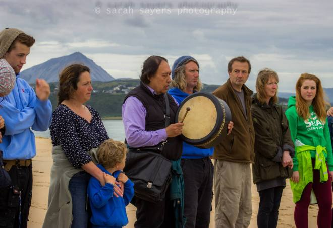 Local people gather with Native American Indian Gary (White Deer) for special prayers and a blessing of family of whales that died at Ballyness beach, Falcarragh, Donegal (photo courtesy of Sarah Sayers).