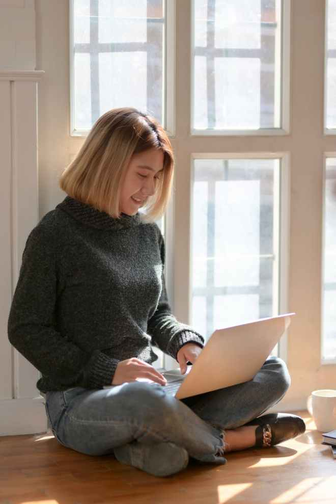 woman in gray sweater sitting on wooden floor typing on portable computer